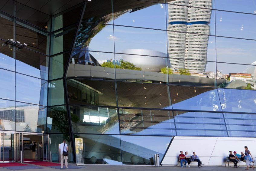 Munich, Germany - August 15, 2013: People relax at the entrance of BMW Welt -BMW World.  On the facade the reflection of BMW towers and museum
